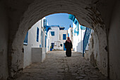 Arabian woman walks through archway along path of buildings with blue windows and white walls in artisan village, Sidi Bou Said, Tunis, Tunisia