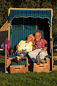 Couple enjoys late afternoon sun in Strandkorb basket along Mainschleife of Main river in autumn, Nordheim, Franconia, Bavaria, Germany