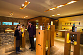 Young woman and man sample wines in Weinreich wine tasting room at Winzerkeller Sommerach winery, Sommerach, Franconia, Bavaria, Germany