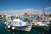 Fishing boats in port with Venetian fortress of Rocca al Mare in distance, Heraklion, Crete, Greece
