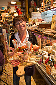 Cheerful waitress serves absolutely delicious antipasti platter at Fratelli Burgio delicatessen shop and restaurant, Syracuse, Sicily, Italy