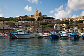 Traditional fishing boats in harbor and Our Lady of Lourdes Church on hillside, Mgarr, Gozo, Malta