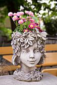 Head-shaped flower pot in beer garden of Brauerei Hartmann brewery and restaurant, Würgau, near Scheßlitz, Franconia, Bavaria, Germany