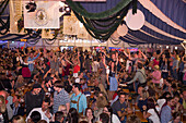 People celebrate in giant beer tent at Bayreuther Volksfest beerfest and amusement park, Bayreuth, Franconia, Bavaria, Germany