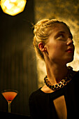 Woman sitting alone at night club bar looking away expectantly