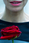 Woman holding single rose, cropped
