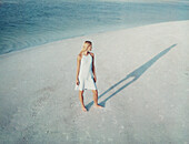 Woman standing on beach contemplating her shadow