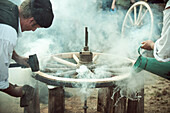 Craftsmen repairing horse-drawn wagon wheel