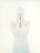 Woman standing with hands on neck, overexposed