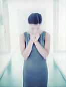 Woman standing with hands under chin, defocused