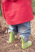 Child wearing raincoat and rubber boots, cropped