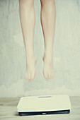 Woman's legs floating above bathroom scale
