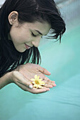Young woman holding flower cupped in hands