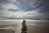 Langzeitbelichtung eines wolkigen Himmels und der Ostsee mit Buhnen im Nationalpark Vorpommersche Boddenlandschaft, Ahrenshoop, Fischland-Darß-Zingst, Mecklenburg Vorpommern, Deutschland