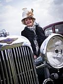 Besucherin freut sich über den passenden Hut zum Lagonda Familienerbstück, Goodwood Revival 2014, Rennsport, Autorennen, Classic Car, Goodwood, Chichester, Sussex, England, Großbritannien
