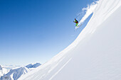 freeride skier jumps over snow cornice, Zugspitze, Hochwanner in the background, Upper Bavaria, Germany