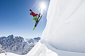 freeride skier jumps over snow cornice, Zugspitze, Hochwanner and Gatterl in the background, Upper Bavaria, Germany