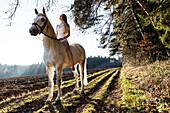 girl in a white dress riding her horse, Freising, Bavaria, Germany