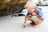 boy writing in the sand, beach at Calo des Moro, tourist, child, childhood, 4 years, Mediterranean Sea, MR, near Santanyi, Majorca, Balearic Islands, Spain, Europe