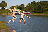 Two girls jump into the Dortmund-Ems-Kanal at lock Große Schleuse Bevergern ,  Muensterland , North Rhine-Westphalia , Germany , Europe
