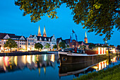 View over river Trave at night towards the old town with the church of St Mary and church of St. Peter, Hanseatic City, Luebeck, Schleswig-Holstein, Germany