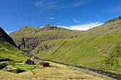 Stream, weekend houses and a lake in Saksun, Streymoy Island, Faroe Islands