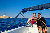 Two young women sitting behind the steering wheel of a sailing yacht steering it past the Cap Figuera with its lighthouse Faro Cala Figuera, Palma de Mallorca is still visible in the background, Balearic Islands, Spain, Europe