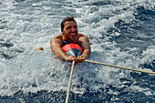 A young man being dragged by a sailing yacht, surfing on an inflatable shark, Mallorca, Balearic Islands, Spain, Europe