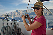 A young woman with hat and sunglasses sitting on a sailing yacht, Mallorca, Balearic Islands, Spain, Europe