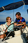 A young woman sitting at the steering wheel, rudder of a sailing yacht, a young man is sitting behind her, Mallorca, Balearic Islands, Spain, Europe
