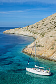 Anchoring sailing yacht in a lonely bay on the greek island Syphnos (Sifnos), Aegean, Cyclades, Greece