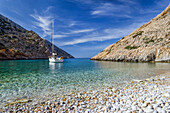 Anchoring sailing yacht in a lonely bight with pebble beach, greek island, Syphnos (Sifnos), Aegean, Cyclades, Greece