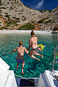Two young women jumping from the back of an anchoring sailing yacht into the water of a lonely bay on the greek island Syphnos (Sifnos), Aegean, Cyclades, Greece