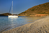 Sunrise above an anchoring sailing yacht in a lonely bay on the greek island Kithnos, Kolona, Aegean, Cyclades, Greece