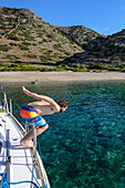 Man diving off a sailing yacht into a lonely bay of the greek island Kithnos, Kolona, Aegean, Cyclades, Greece