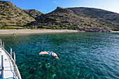 Man diving off a sailing yacht into a lonely bay off the greek island of Kithnos, Kolona, Aegean, Cyclades, Greece