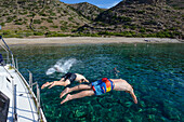 Young men diving off a sailing yacht into a lonely bay off the greek island of Kithnos, Kolona, Aegean, Cyclades, Greece