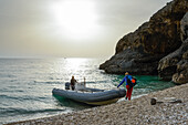 Young woman with trekking gear embarking an inflatable boat on the pebble beach of the bay Cala Sisine that will bring her back to the starting point of the Selvaggio Blu, Golfo di Orosei, Sardinia, Italy, Europe