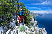 A young woman with trekking gear hiking along the mountainous coast above the sea, Golfo di Orosei, Selvaggio Blu, Sardinia, Italy, Europe
