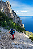A young woman with trekking gear hiking down a steep slope along the mountainous coast above the sea, Golfo di Orosei, Selvaggio Blu, Sardinia, Italy, Europe