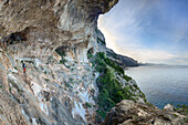 Woman with trekking gear standing in huge caves above the sea, in mountainous coastal landscape, Golfo di Orosei, Selvaggio Blu, Sardinia, Italy, Europe
