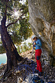 A young woman with climbing gear and a rope after abseiling in the mountainous coastal landscape above the sea, Golfo di Orosei, Selvaggio Blu, Sardinia, Italy, Europe
