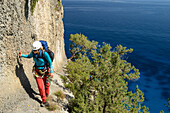 A young woman with trekking gear walking on an exposed ridge in the mountainous coast above the sea, Golfo di Orosei, Selvaggio Blu, Sardinia, Italy, Europe