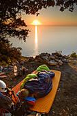 Young woman sleeping in her sleeping bag on a charcoal burners' circle at sunrise near the bay Cala Biriola, Trekking- and climbing gear visible, Golfo di Orosei, Selvaggio Blu, Sardinia, Italy, Europe