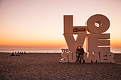 Couple taking a selfie photograph with smartphone in front of Love sculpture on the beach at sunset, Ostend, Flanders, Flemish Region, Belgium