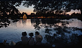 Three schoolgirls chatting on the banks of Hoan Kiem Lake with Thap Rua temple in the background, Hanoi, Vietnam, Asia