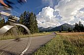 Junge Frau fährt Fahrrad in der Nähe der Berge an einem sonnigen Tag, Tannheimer Tal, Tirol, Österreich