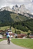 Junge Frau fährt mit ihrem Fahrad in der Nähe der Berge an einem sonnigen Tag,  Rote Flöh, Gimpel, Hochwiesler, Tannheimer Tal, Tirol, Österreich