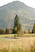 Junge Frau fährt mit ihrem Fahrad in der Nähe der Berge an einem sonnigen Tag, Tannheimer Tal, Tirol, Österreich