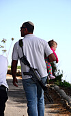 Israeli man carrying weapon and child, Israel